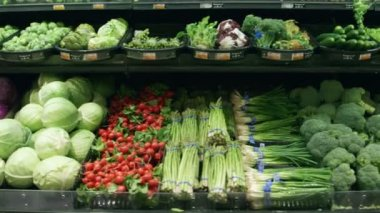 Medium shot moving past fresh vegetables in a supermarket grocery — Stock Video