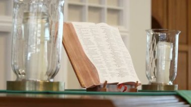 Bible and two candles on a church altar — Stock Video