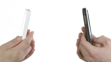 Two hands holding black and white smartphones — ストックビデオ