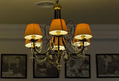 Beautiful chandelier with the orange lamp shade — Stok fotoğraf