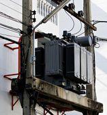 Grey transformer mounted on power poles — Stock Photo