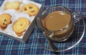 Cup of coffee and cookies on chintz Scots. — Stockfoto