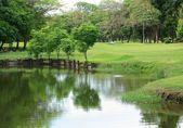Bangkok City Park colorful trees with reflection and people in lawn. — Stock Photo