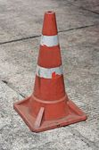 Old traffic cone on bitumen pavement — Stock Photo