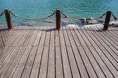 Empty wooden jetty on the lake shore — Stock Photo