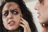 Beaten up girl looking in the mirror — Stock Photo