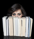 Girl hiding behind book shelf — Stock Photo