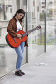Girl playing guitar in the city — Stock Photo