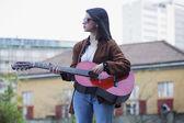 Girl playing guitar in urban scene — Stock Photo