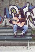 Meisje, zittend op een bankje en gitaar spelen — Stockfoto