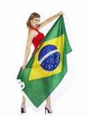 Sensual football supporter holding Brazil flag — Stock Photo