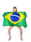 Sensual football supporter holding Brazil flag and looking — Stok fotoğraf