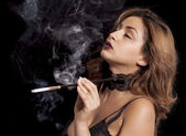 Sexy woman with cigarette holder smoking — Stock Photo