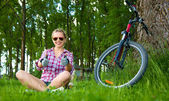 Young cyclist sitting in the grass and showing thumbs up gesture — Foto Stock