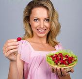 Smiling woman holding raspberries — Stock Photo
