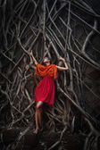 Girl in tree roots — Stock Photo