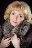 Middle-aged woman posing in fur vest — Stock Photo