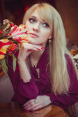 Girl posing near flowers — Stock Photo
