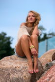 Girl sitting on rock — Stock Photo