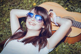 Girl with the guitar lying on the grass — Stock Photo