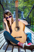 Girl with the guitar on the bridge — Stock Photo