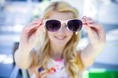 Girl showing sunglasses to the camera — Stockfoto