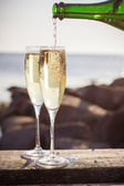 Pouring champagne into glasses — Stock Photo