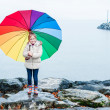Cute little girl under rain with colorful umbrella — Stock Photo