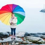Cute little girl under rain with colorful umbrella — Stock Photo