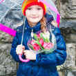 Portrait of a cute little girl on a rainy day, holding, umbrella and bouquet of pink tulips — Stock Photo