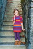 Beautiful little girl sitting on steps,  wearing colorful dress — Stock Photo