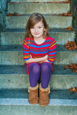 Beautiful little girl sitting on steps,  wearing colorful dress — Stock Photo