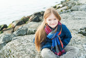 Portrait of a cute little girl next to lake on a nice day — Stock Photo