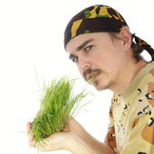 Young man eating grass — Stock Photo