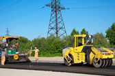 Workers with rolling machinery making asphalt — Stock Photo