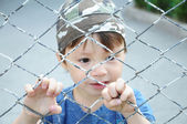 Boy behind bars — Stock Photo