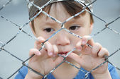 Boy thinking behind bars — Stok fotoğraf