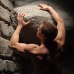 Постер, плакат: Strong man holding stone