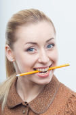 Excited attractive woman biting pencil — Stock Photo