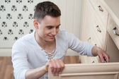 Young man assembling furniture — Stock Photo