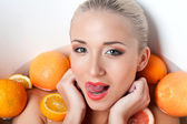 Woman posing in the bathtub with  oranges — Photo