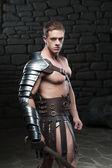 Gladiator with sword posing — Stock Photo