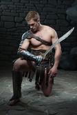Gladiator with sword kneeling — Stock Photo