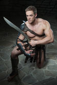 Gladiator with sword kneeling — 图库照片