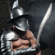 Gladiator in helmet and armour holding sword — Stock Photo #50370295