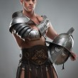Gladiator in armour posing with helmet over grey background — Stock Photo #50370571
