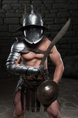 Gladiator in helmet and armour holding sword — Stock Photo