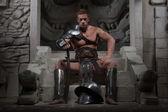Gladiator in armour sitting on steps of ancient temple with helm — Stock Photo