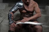 Gladiator in armour sitting on steps of ancient temple looking a — Stock Photo