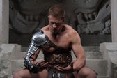 Gladiator in armour sitting on steps of ancient temple — Stock Photo